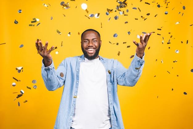 Zwycięzca! rozochocony amerykanina afrykańskiego pochodzenia młody człowiek tanczy nad żółtym tłem.