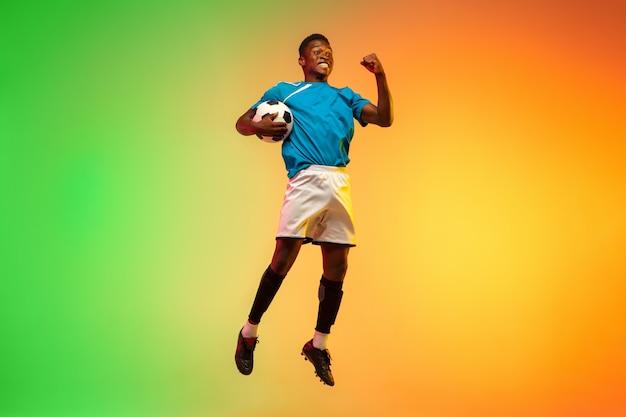 Zwycięzca skoków wzwyż. męska piłka nożna, trening piłkarza w akcji na białym tle na gradientowym tle studio w świetle neonowym. pojęcie ruchu, działania, osiągnięć, zdrowego stylu życia. kultura młodzieżowa.