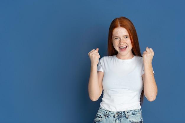 Zwycięzca, świętuje. portret młodej dziewczyny rasy kaukaskiej na niebieskiej ścianie