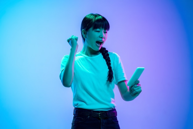 Zwycięzca z telefonem. portret młodej kobiety azjatyckiej na gradientowym niebiesko-fioletowym tle studio w świetle neonowym. pojęcie młodości, ludzkie emocje, wyraz twarzy, sprzedaż, reklama. piękna brunetka modelka.