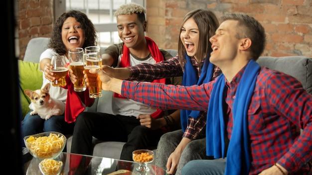 Zwycięzcy. podekscytowani ludzie oglądają mecz, mistrzostwa w domu. wieloetniczna grupa przyjaciół, kibiców kibicujących ulubionej narodowej koszykówce, tenisie, piłce nożnej, drużynie hokejowej. pojęcie emocji.
