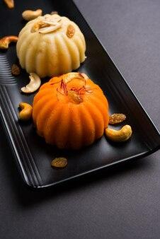 Zwykła lub szafranowa semolina lub soji halwa znana również jako sweet rava sheera or shira - indyjskie słodycze na festiwal przyozdobione suszonymi owocami. podawane w talerzu lub misce, selektywne skupienie