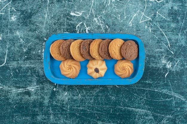 Zwykłe i czekoladowe ciasteczka na drewnianej tacy, na niebieskim tle. zdjęcie wysokiej jakości