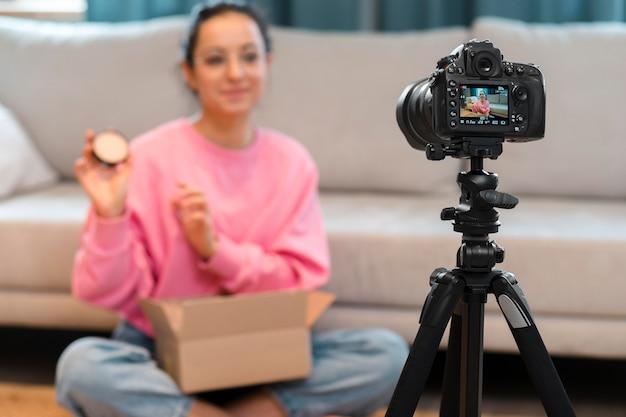 Zwykły bloger w okularach przed kamerą i rozpakowywujący