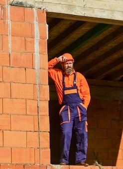 Zwykły dzień. codzienna rutyna na budowie. bardzo dobrze. mechanik zmęczony budowniczy relaks na budowie. konstruktor palenia papierosów. przerwij się i zrelaksuj. brodaty mężczyzna w mundurze inżyniera i kasku.