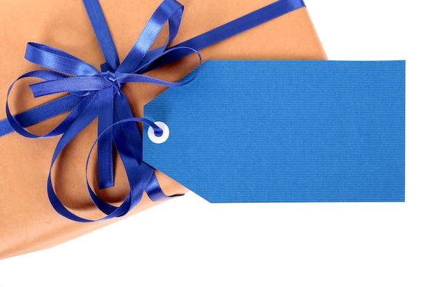 Zwykły papierowy pakunek lub paczka, niebieski podarunkowy tag lub etykieta i wstążka