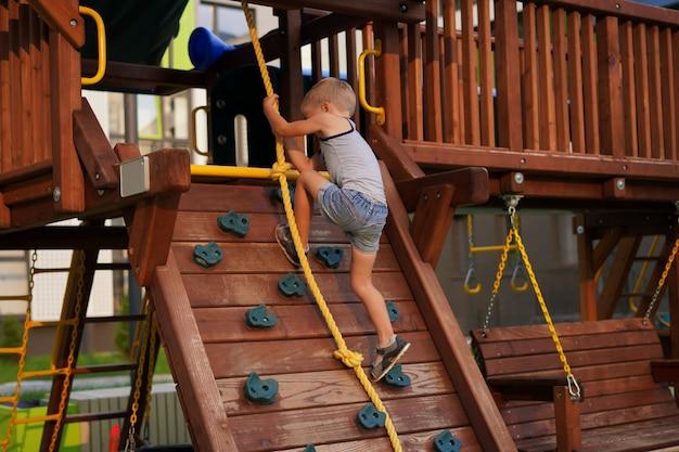 Życie dzieci w nowoczesnym mieście, mały chłopiec bawi się na placu zabaw w pobliżu domu