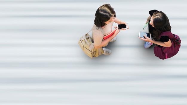 Życie ludzkie w odległości społecznej widok z góry z lotu ptaka z dwiema studentkami ze stojakiem na smartfona