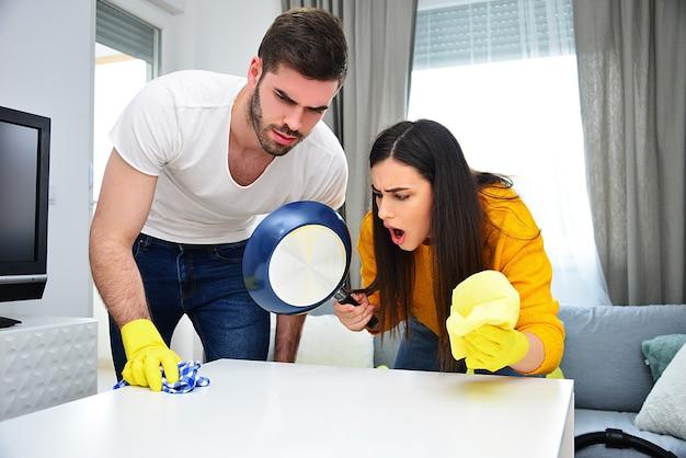 Życie małżeńskie, pary, sprzątanie, prace domowe i koncepcja obowiązków. młody mężczyzna i kobieta razem sprzątają i wycierają dom. e