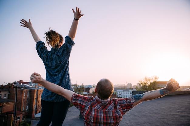 Życie na wolności. szczęśliwa para wolna na dachu. nie do poznania biodrówki oglądając zachód słońca. ulga od problemów, tło miejskie z wolną przestrzenią