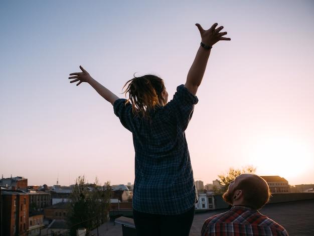 Życie na wolności. ulga od problemów na dachu. nie do poznania hipsterzy oglądający zachód słońca, tło miejskie z wolną przestrzenią, romantyczna randka