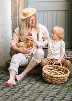 Życie na wsi. wiejski chłopiec z brązowym kurczakiem tatusia i dużym koszem na podwórku przy drzwiach wejściowych. letni dzień