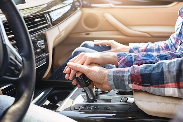 Życie pełne przygód z bliska młodej pary trzymającej się za ręce w rodzinie samochodów
