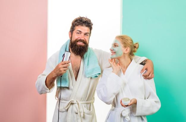 Życie rodzinne mąż i żona brodaty mężczyzna z golarką elektryczną przycinającą brodę szczęśliwa kobieta z