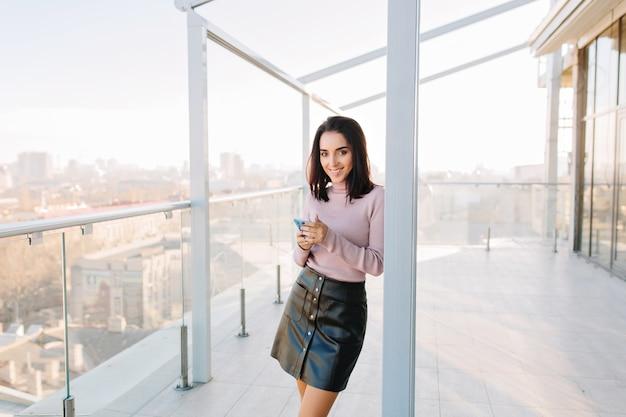Życie w wielkim mieście, słoneczny poranek młodej radosnej kobiety uśmiechającej się na tarasie w penthouse z widokiem na miasto.