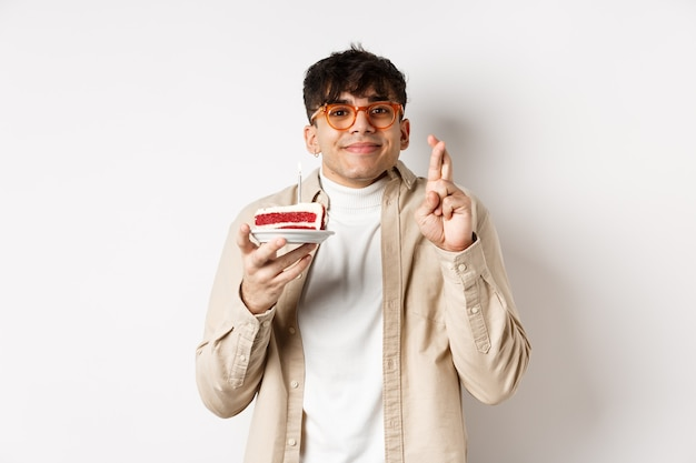 Życzący przystojny facet w okularach życzenia na tort urodzinowy, stojąc z skrzyżowanymi palcami i szczęśliwym uśmiechem na białej ścianie.