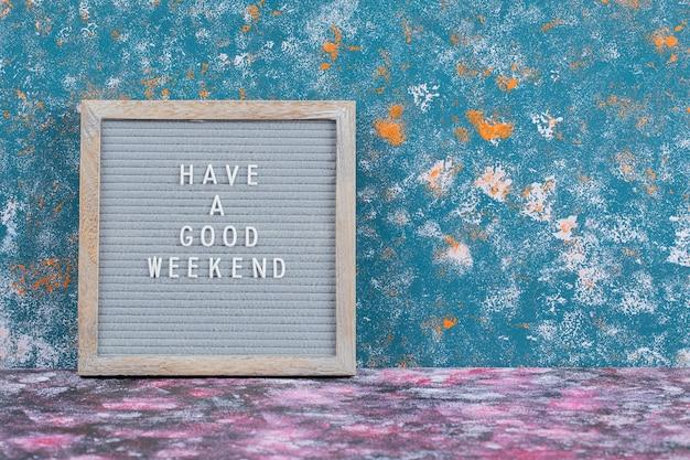Życzę miłego weekendowego plakatu na niebieskiej powierzchni