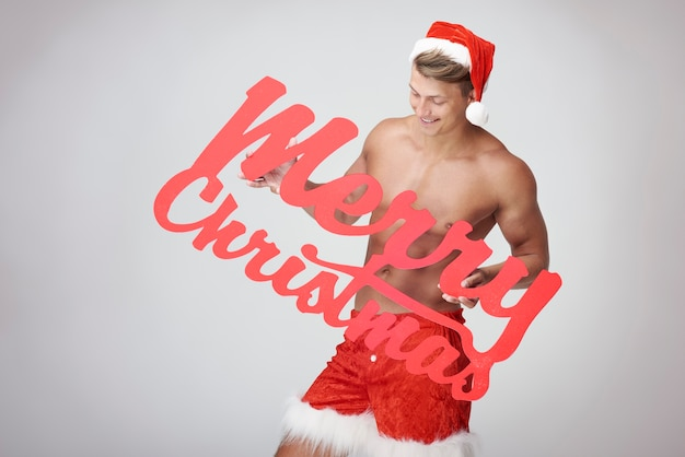 Życzenia bożonarodzeniowe i muskularny mężczyzna