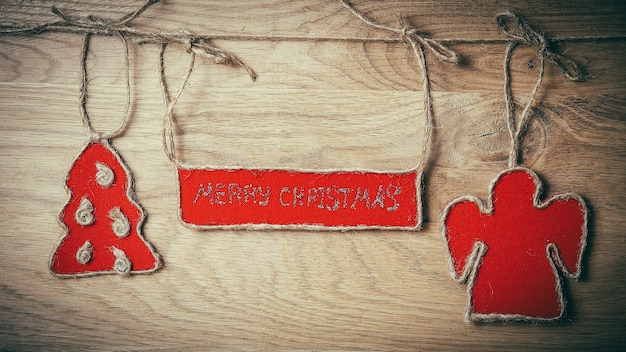 Życzenia bożonarodzeniowe przymocowane do liny na drewnianym tle. miejsce na tekst