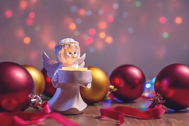 Życzenia bożonarodzeniowe, świeca anioła i wielokolorowe błyszczące kulki.