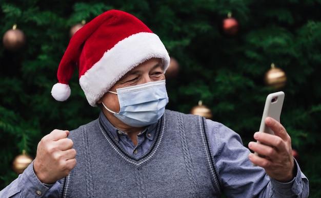 Życzenia świąteczne online. ścieśniać portret starszego mężczyzny w kapeluszu świętego mikołaja i maski medyczne z emocjami. na tle choinki. koronawirus pandemia