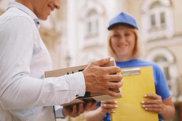 Życzliwa dostawa kobieta w niebieskim mundurze na ulicy miasta