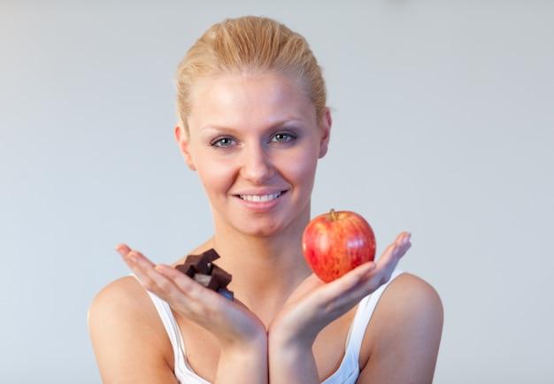 Życzliwa kobieta trzyma czekoladę i jabłczaną ostrość na kobiecie