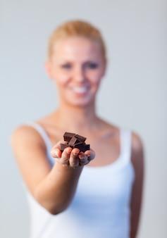 Życzliwa kobieta trzyma czekoladową ostrość na czekoladzie