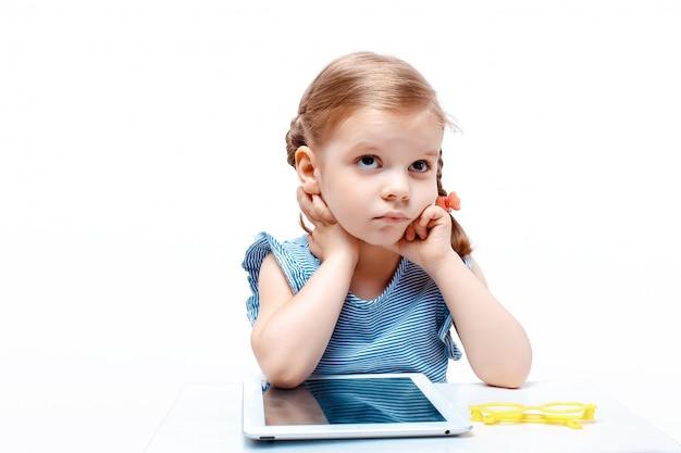 Życzliwa myśląca młoda dziewczyna używa pastylkę podczas gdy siedzący przy stołem, odosobnionym