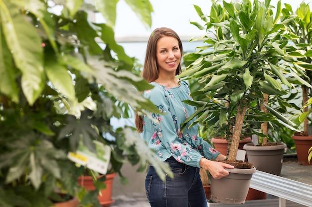Życzliwa uśmiechnięta młoda kobieta kupuje rośliny jukki