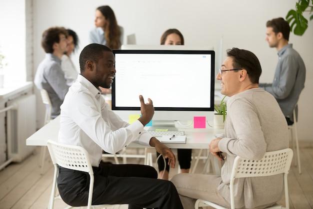 Życzliwi uśmiechnięci różnorodni męscy koledzy ma przyjemną rozmowę przy pracą