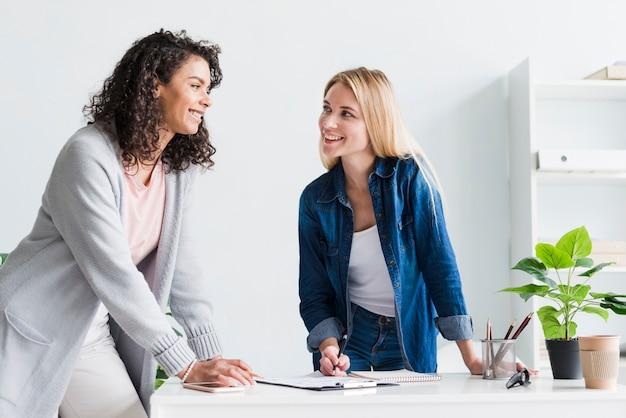 Życzliwi żeńscy koledzy dyskutuje pracę i śmia się przy biurem