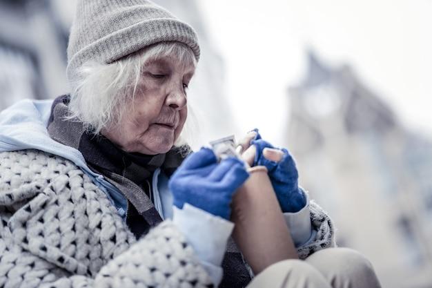 Życzliwość ludzi. miła starsza kobieta bierze pieniądze z kubka i sprawdza, ile ma