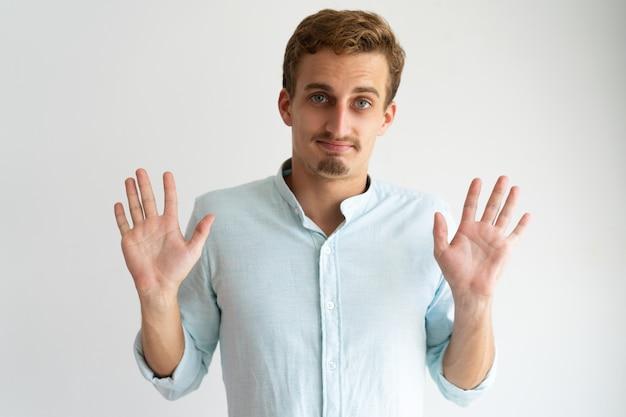 Życzliwy facet w białej przypadkowej koszula gestykuluje grzywnę, ty wygrywasz.