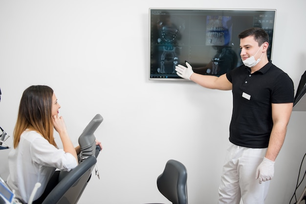 Życzliwy męski dentysta pokazuje żeńskiemu pacjentowi jej stomatologiczny promieniowanie rentgenowskie wizerunek na komputerowym monitorze