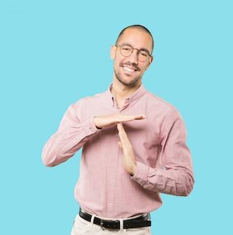 Życzliwy młody człowiek robi czasowi gestowi z rękami