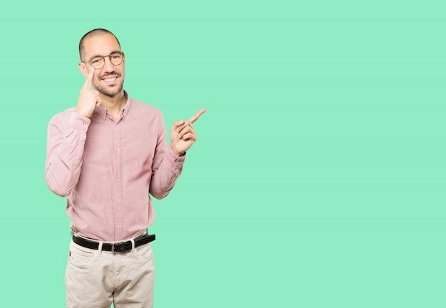 Życzliwy młody człowiek robi gestowi ostrożność z ręką wskazującą na jego oko