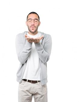 Życzliwy młody człowiek robi gestowi wysyłać buziaka ręką