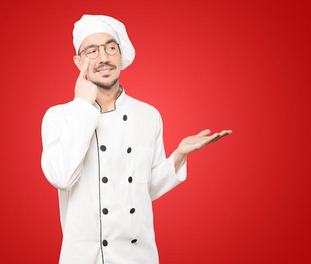 Życzliwy młody szef kuchni robi gest uważności z ręką wskazującą na oko