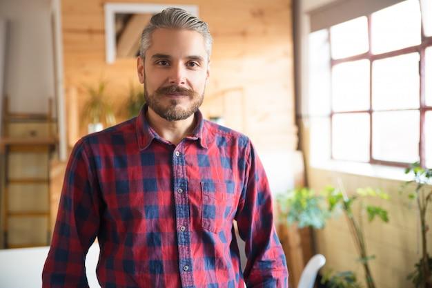 Życzliwy przedsiębiorca pozuje w nowoczesnym biurze