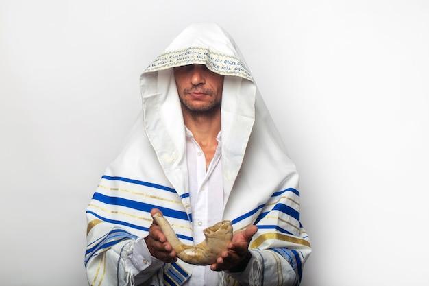 """Żyd owinięty w szal modlitewny tallit z napisem po hebrajsku """"baruch atah adonai"""", trzymający szofar (róg). rosz ha-szana (żydowski nowy rok), koncepcja szabatu i jom kippur"""