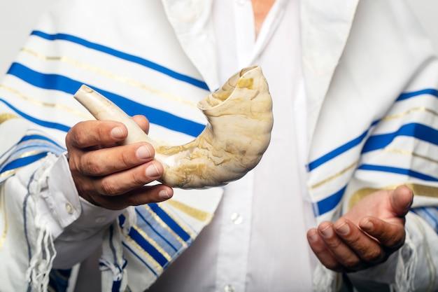Żyd owinięty w talit, modlitewny szal trzymający szofar (róg). koncepcja rosz haszana (żydowski nowy rok), szabat i jom kippur. rabin trzymający w ręku szofar przed świętami tiszrei