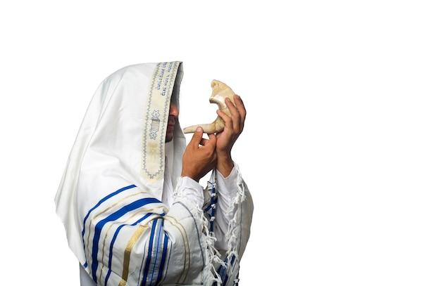 """Żyd rabin w tałesie z napisem """"baruch atah adonai"""" napisanym po hebrajsku, dmuchający w szofar, barani róg rosz haszana (nowy rok) dobry na białym tle. prawosławni w tałesie"""