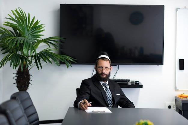 Żyd w jarmułce i okularach siedzi przy stole w biurze