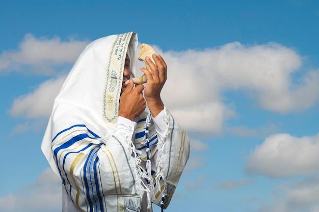 """Żyd w tałesie, szal modlitewny z napisem po hebrajsku """"baruch atah adonai"""", dmuchający w szofar, barani róg rosz ha-szana (nowy rok), jom kippur na tle błękitnego nieba i chmur"""