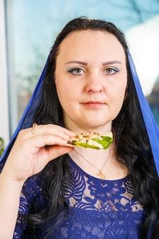 Żydówka z głową okrytą niebieską peleryną przy stole sederowym je moror hazeret macy