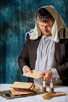 Żydowscy mężczyźni błogosławią przaśny chleb matzah, który świętują seder