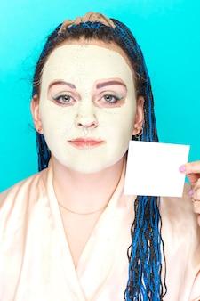 Żydowska kobieta z niebieskimi afro warkoczami, twarz w zamarzniętej masce z zielonej gliny z wizytówką w dłoniach na niebieskiej powierzchni