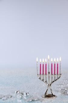 Żydowska menora świecznik z płonącymi świecami na białej powierzchni. święto chanuka.