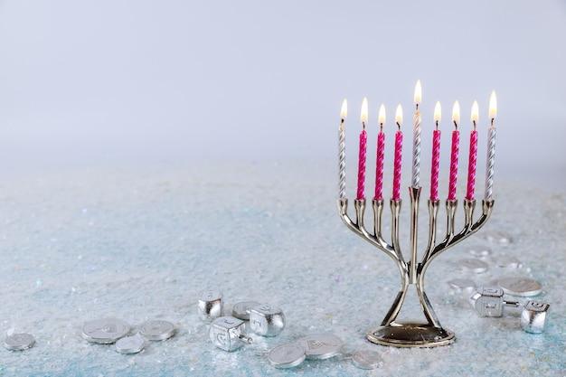 Żydowska menora świecznik z płonącymi świecami na tle blasku. święto chanuka.